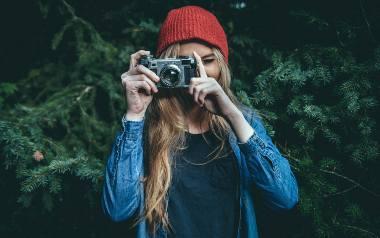 Blondynka w czerwonej czapce, zwrócona w stronę widza, robi zdjęcie aparatem fotograficznym.