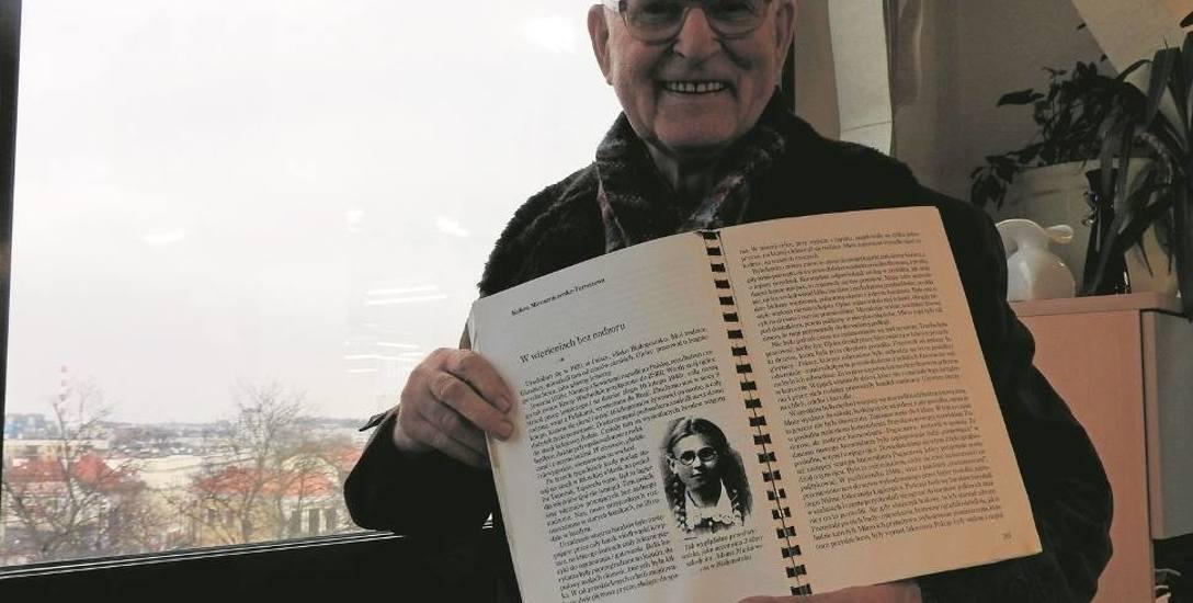 """Jacek Szczepański, trzymający publikację """"Przeznaczeni na zagładę. Wspomnienia polonijnych Sybiraków"""". Znajdują się w niej m. in. relacje osób, które"""