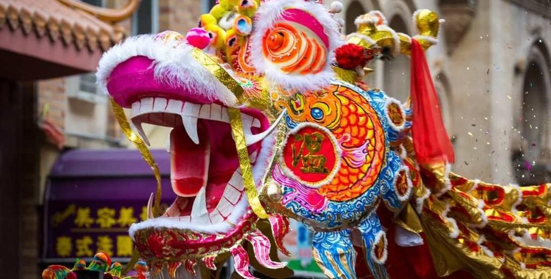 Bajecznie kolorowe chińskie smoki tańczą na ulicach miast