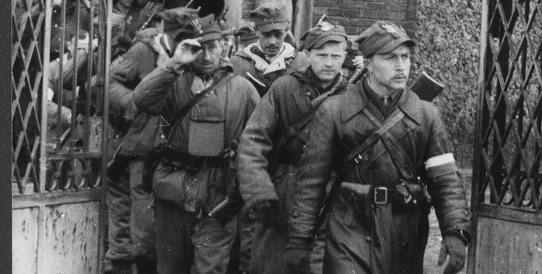 """kompania szturmowa 3 Brygady Wileńskiej AK wychodzi z kościoła w Turgielach, na czele ppor. Romuald Rajs """"Bury"""""""
