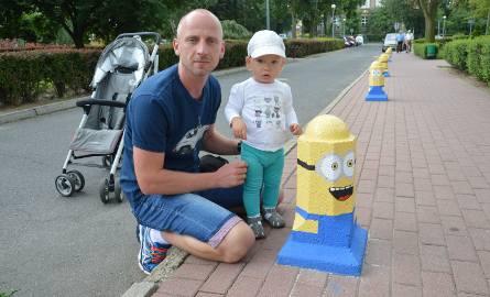 Pan Remigiusz z dzieckiem na tle Minionków przy ul. Poczdamskiej