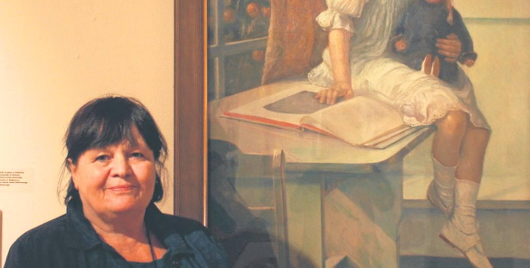 """Gizela Chmielewska. W tle przygotowana wspólnie z mężem Bogdanem wystawa """"Wypominki Kresowe"""", 2016 r."""