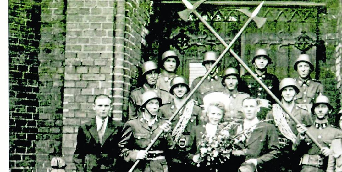 """Ślub strażaka w kościele Najświętszego Zbawiciela. Na odwrocie zdjęcia jest pieczątka : """"Foto Ira"""" - Stanisław Prokopiuk, Ustka, ul. Stalina Nr. 31."""