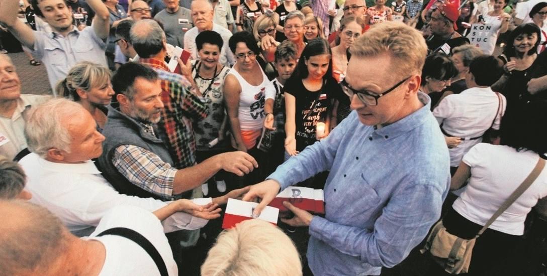 Poseł Stasiński (na zdj. rozdaje pamiątkowe opaski): - Przyszliśmy uczcić powstańców. Manifestacja była naprawdę spokojna. Nie rozumiem działań policji.