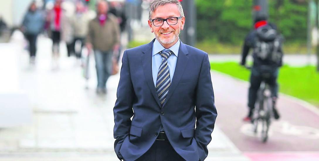 Prof. Jacek Szołtysek na alei Korfantego w Katowicach. Aleją jeżdżą auta, autobusy i tramwaje, jest i pas dla rowerzystów