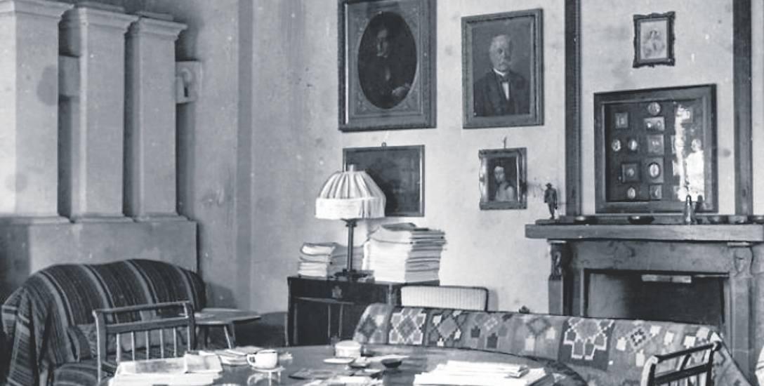 Salonik w starym dworze to m.in. stół z fotelami i kanapą, kominek z półką na bibeloty i obrazy przodków na ścianie