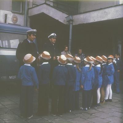 Milicjanci rozmawiają z dziećmi ubranymi w specjalne ostrzegawcze kapelusiki przed budynkiem szkoły. Widoczny fragment samochodu Nysa 522 należacego