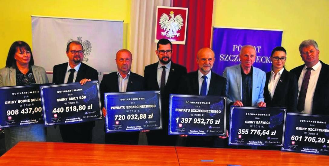 Samorządowcy z powiatu szczecineckiego z symbolicznymi czekami na dofinansowanie inwestycji drogowych po podpisaniu umowy z wicewojewodą