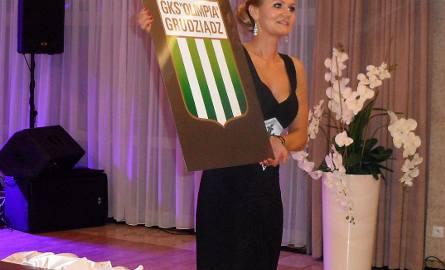 Joanna Kapusta zachęca do licytowania planszy z logo GKS Olimpia Grudziądz.