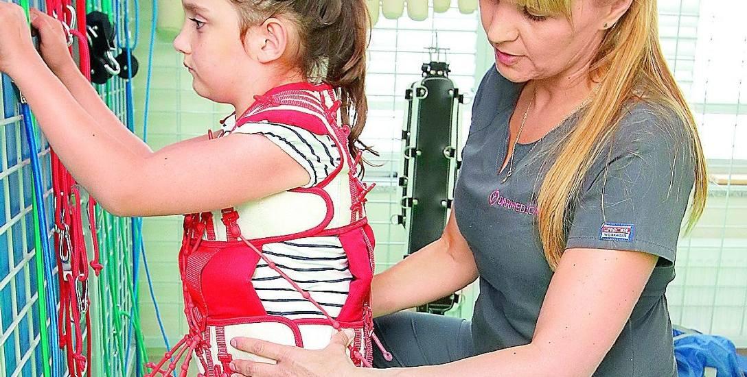 Siedmioletnia Julka już po pierwszych dwóch tygodniach terapii TheraSuit w DarMedice poprawiła swój wzorzec chodu i postawy. Na zdjęciu z fizjoterapeutką