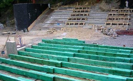 """Nowy amfiteatr zostanie otwarty za miesiąc. Na razie pokazuje swoje """"trzewia"""". Na zielonych belkach będą deski sceny, w głębi wylane ławy widowni i jeden"""
