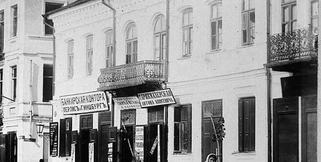 """Dom Abrama Markusa w 1897 r. - widoczne szyldy księgarni Kaufmana, fryzjera Anisiewicza i kantoru """"Perlisa i Ginzburga""""."""